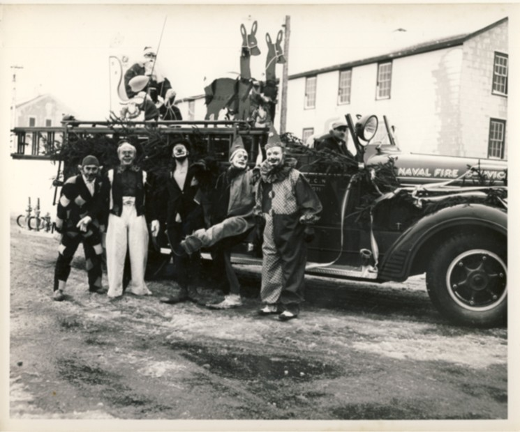 Image for Photograph of R.C.N. Naval Fire Service, fire engine made into a Christmas float with one Santa Claus and five clowns.