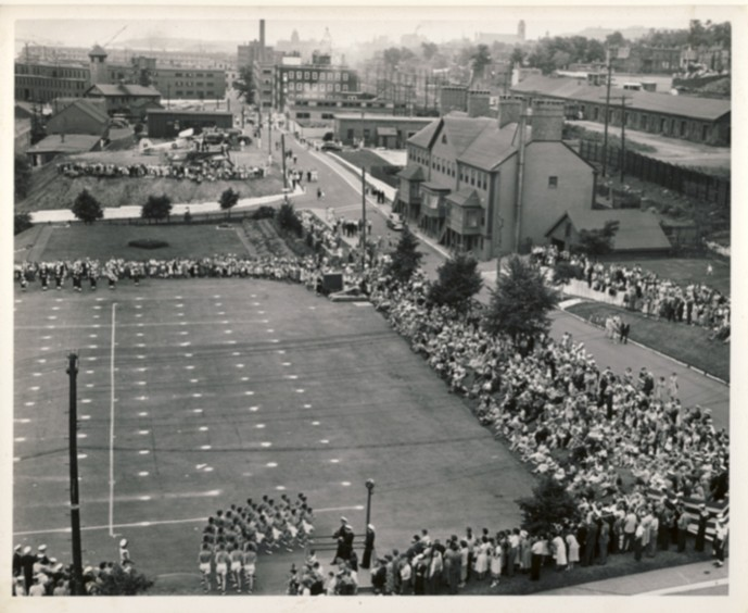 Image for RCN Photograph of the Ceremonies during Navy Week and the Halifax Bicentenary in HMC Dockyard/CFB Halifax,  August 8th to 13th, 1949 [Men entering parade ground for a gymnastic performance and view of the dockyards]