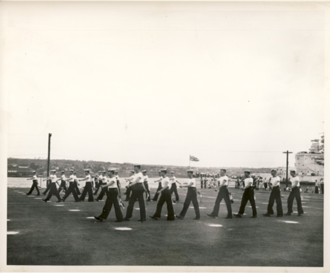 Image for RCN Photograph of the Ceremonies during Navy Week and the Halifax Bicentenary in HMC Dockyard/CFB Halifax,  August 8th to 13th, 1949 [Sailors marching on parade ground with HMS Glasgow and Dartmouth in the background]
