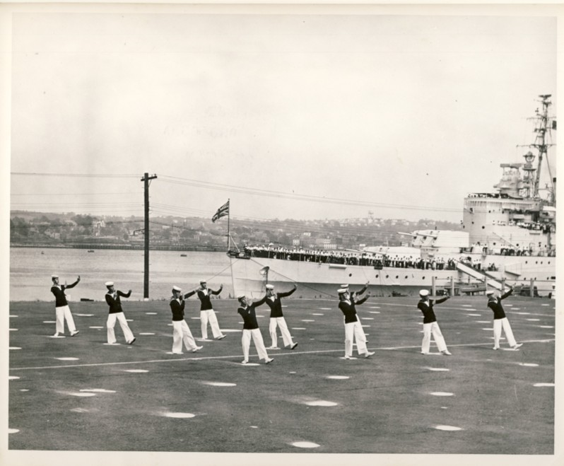 Image for RCN Photograph of the Ceremonies during Navy Week and the Halifax Bicentenary in HMC Dockyard/CFB Halifax,  August 8th to 13th, 1949 [Sailors doing a dance routine on parade ground with HMS Glasgow and Dartmouth in the background]