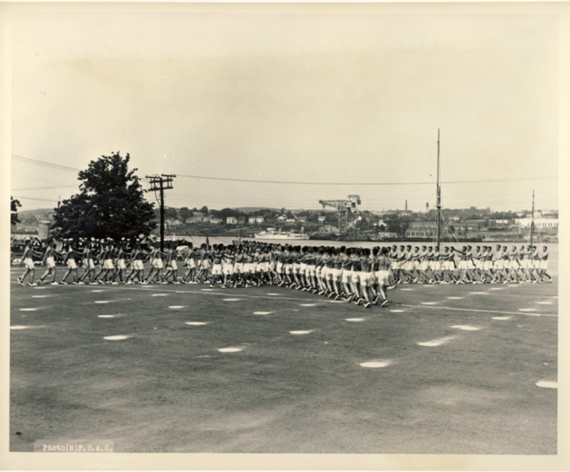 Image for RCN Photograph of the Ceremonies during Navy Week and the Halifax Bicentenary in HMC Dockyard/CFB Halifax,  August 8th to 13th, 1949 [Men in shorts marching on parade ground with Dartmouth, Nova Scotia in back ground]