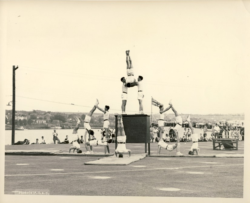 Image for RCN Photograph of the Ceremonies during Navy Week and the Halifax Bicentenary in HMC Dockyard/CFB Halifax,  August 8th to 13th, 1949 [Sailors doing a gymnasyic routine parade ground with HMS Glasgow and Dartmouth in the background]