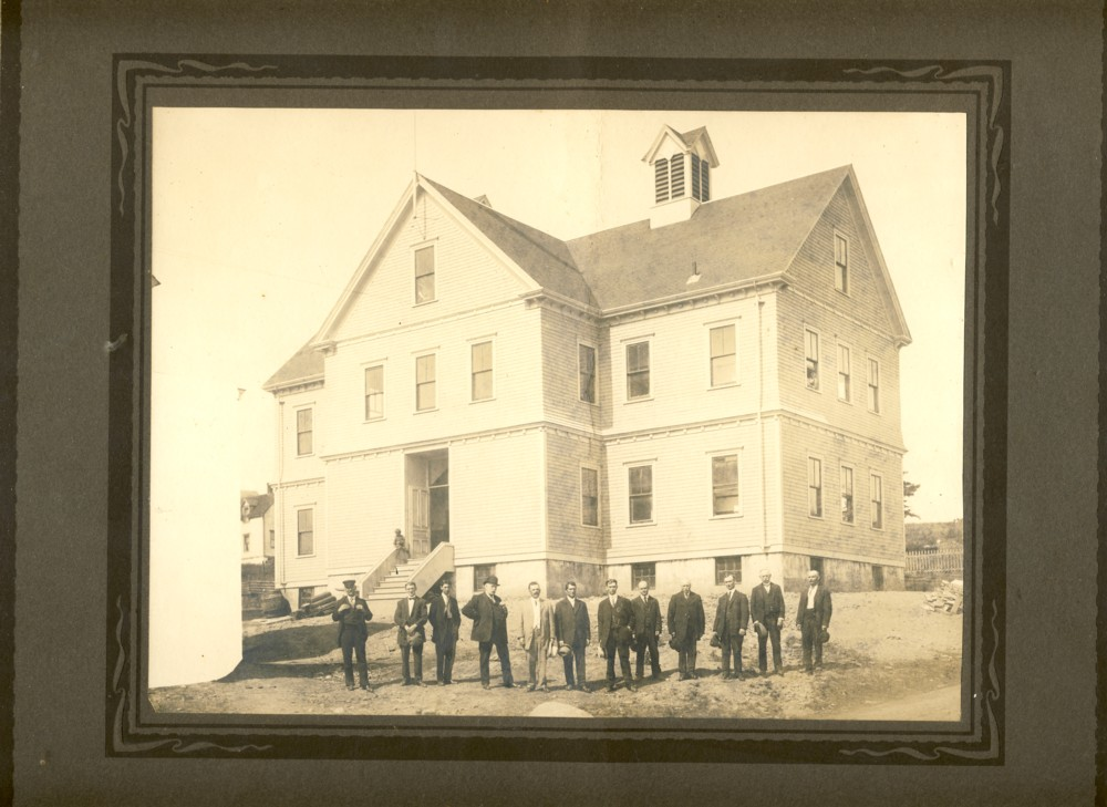 Image for Photograph of large wooden school with school board members in foreground.  One child in window on the right and one on the front step.