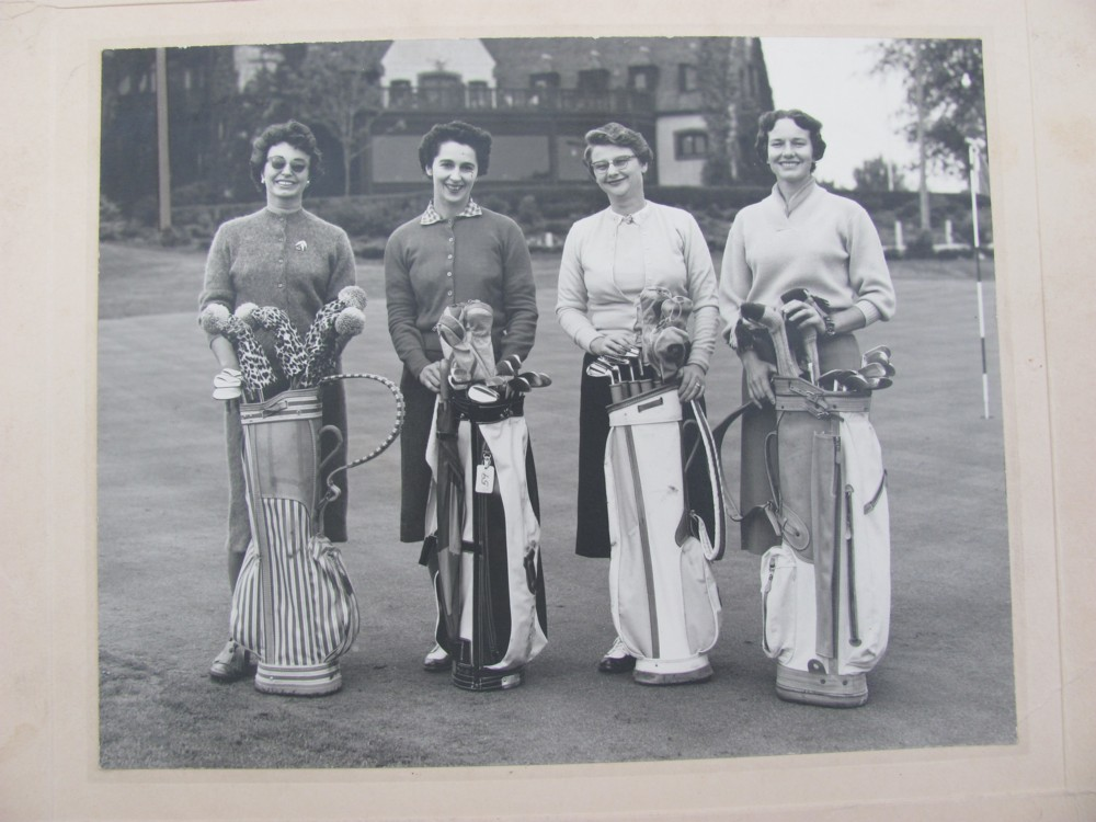 Image for Photograph women's golf foursome with golf clubs and clubhouse in the background