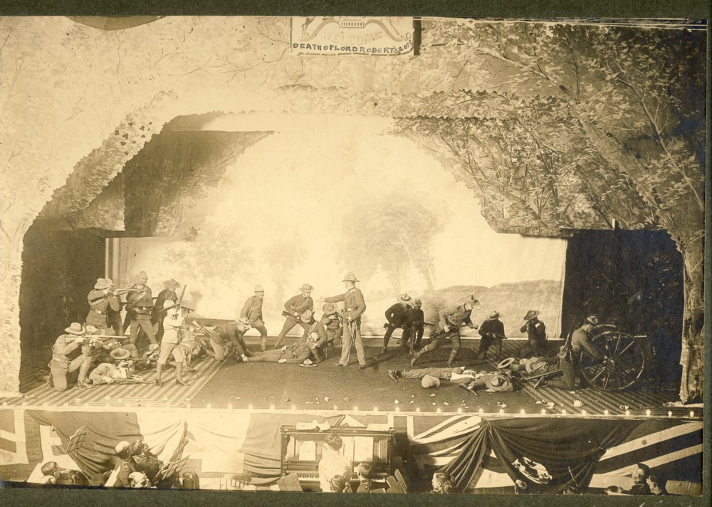 Image for 'The Death of Lord Robert's Son'.  A photograph of an reenactment of Frederick Hugh Sherston Roberts death done on stage with military band in an orchestra pit in the foreground