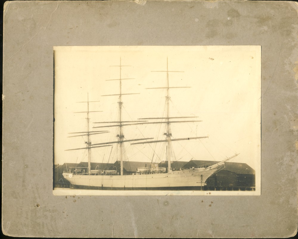 Image for Photograph of sailing ship at a wharf with warehouses in the foreground. Written in pencil on the verso is 'Ship at Shipyard, Bridgewater, Note Figurehead.'